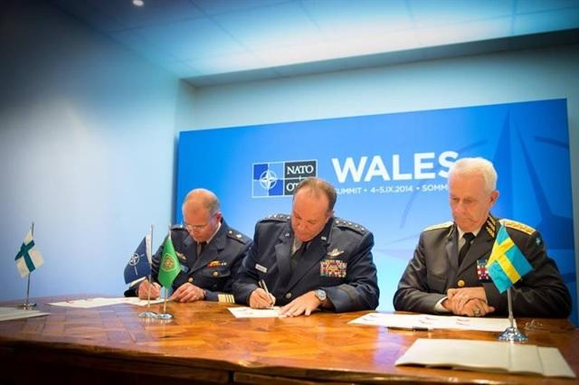 Puolustusvoimain komentaja kenr Jarmo Lindberg (vas), Naton Euroopan joukkojen komentaja kenr Phil Breedlove (kesk), ja Ruotsin asevoimien ylipäällikkö kenr Sverker Göranson allekirjoittavat Host Nation Support -sopimuksen Naton Walesin huippukokouksessa 2014.